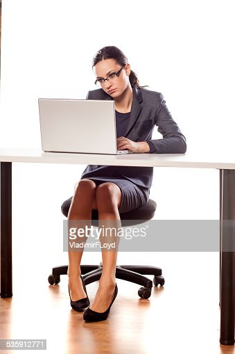 Serious business woman sitting at a table with a laptop : Stock Photo