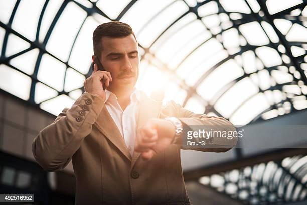 Ernst Geschäftsmann, die die Zeit während der Telefongespräche.