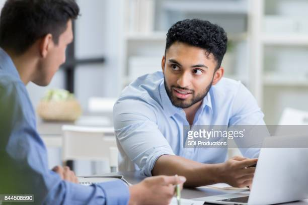 Serious businessman discusses something with male colleague