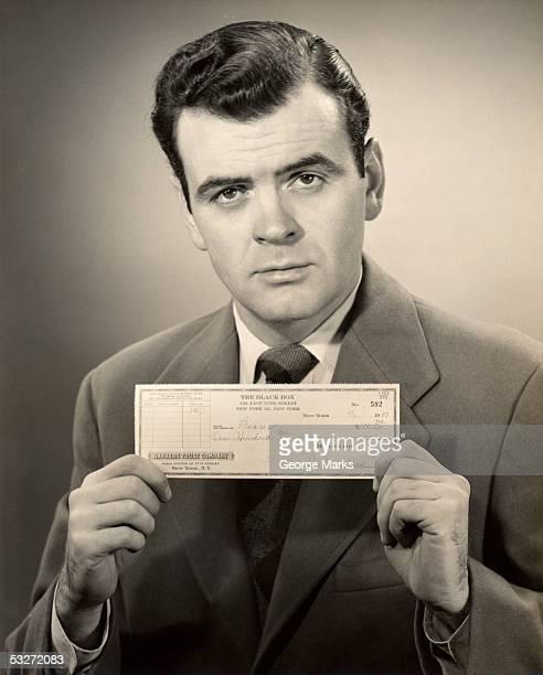 Serious businessman displaying bank check