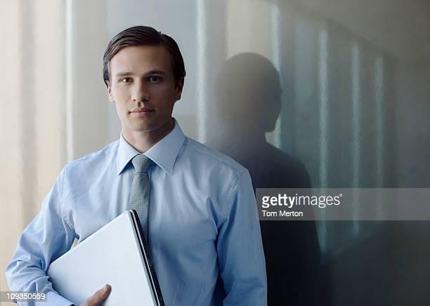 Serious businessman holding laptop