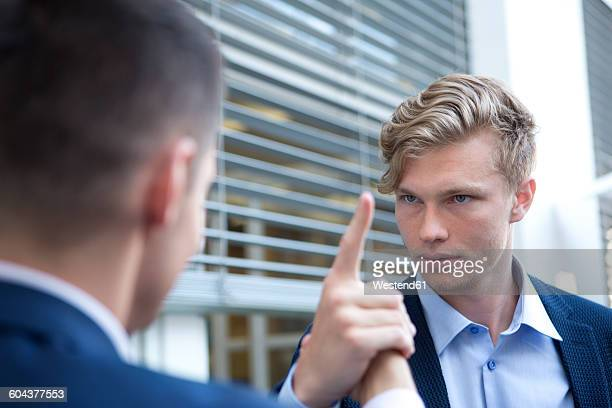 Serious businessman looking at colleague outdoors