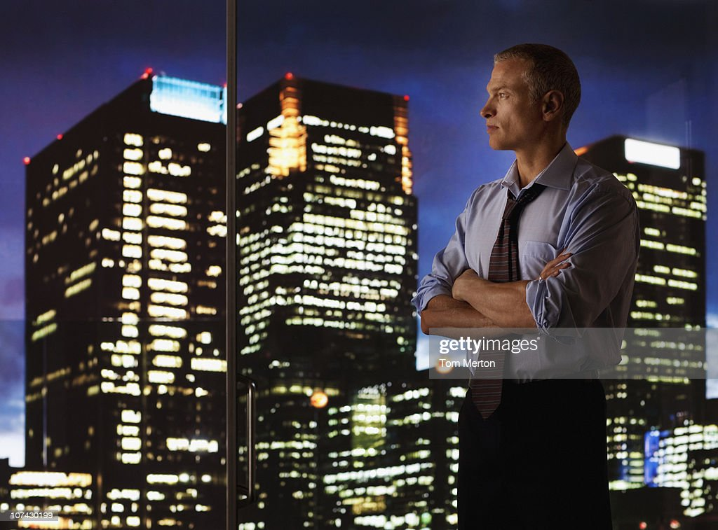 Serious businessman looking out glass wall at night cityscape : Stock Photo