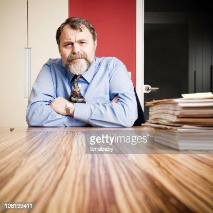 Ernst Geschäftsmann sitzt am Schreibtisch mit Zeitungen
