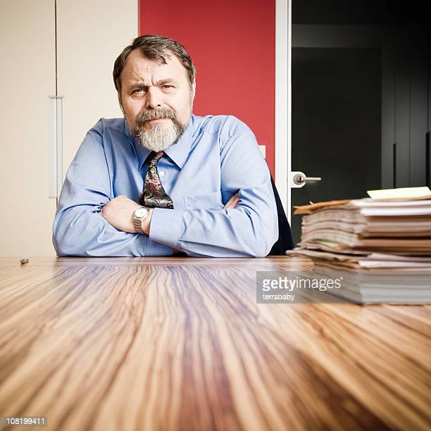 Serious Businessman Sitting at Desk with Papers