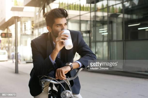 Homme d'affaires grave assis sur le vélo et de boire du café.