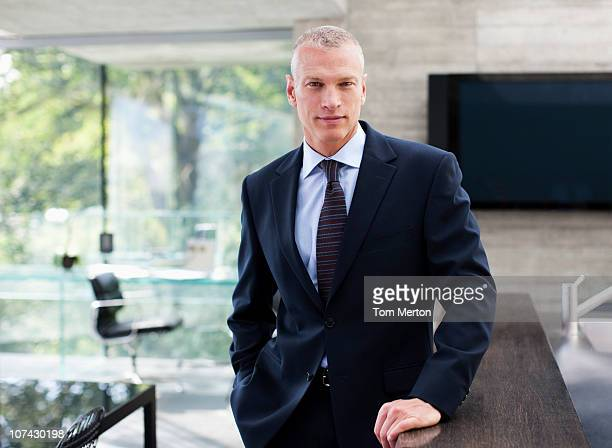 Serious businessman standing at counter in conference room
