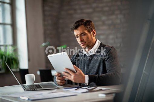 Serious businessman using touchpad while working in the office. : Stock Photo