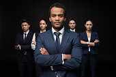 Serious businessman with his business colleagues standing with arms crossed and looking at camera isolated on black
