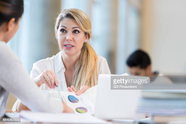 Serious businesswoman discusses something with colleague
