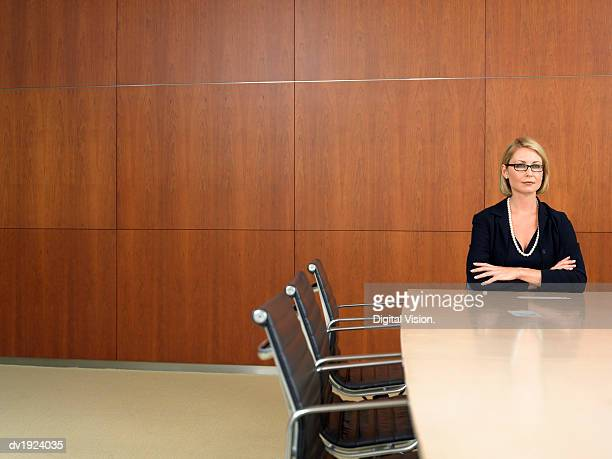 Serious Businesswoman Sitting at the End of a Conference Room Table