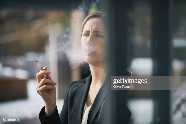 Serious businesswoman smoking a cigarette at the window