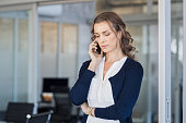 Serious business woman looking worried while talking on the phone in conference room. Frustrated businesswoman in office using mobile phone. Unhappy mature woman talking on phone call on smartphone.