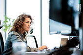Serious mature businesswoman using computer at desk. Female professional is sitting in office. She is wearing smart casuals.