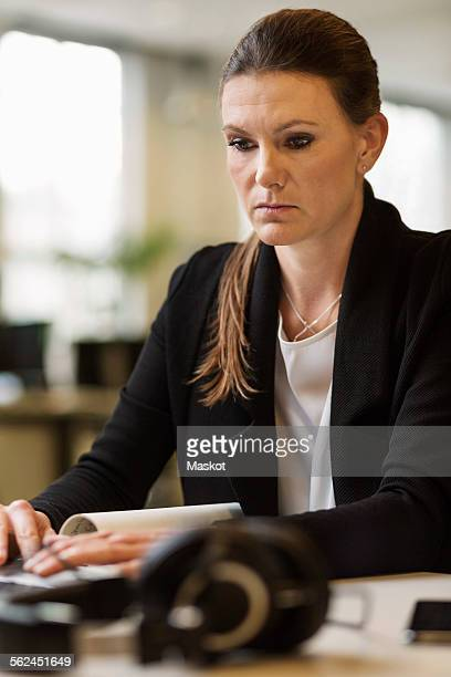 Serious businesswoman using laptop at desk in creative office