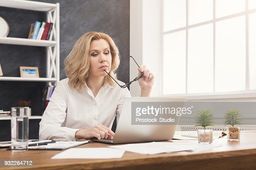 Serious businesswoman working on laptop at office : Stock Photo