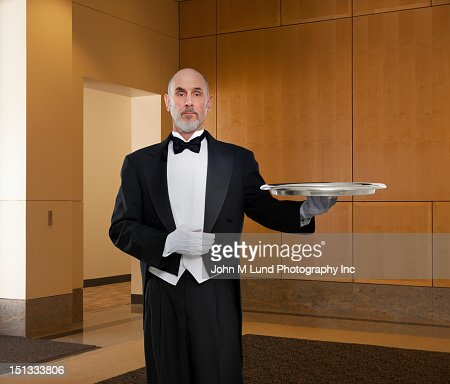 Serious butler holding tray