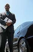 Serious Car Salesman Stands Next to a Black Car Holding a Clipboard