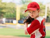 Serious Caucasian boy preparing to pitch in baseball game