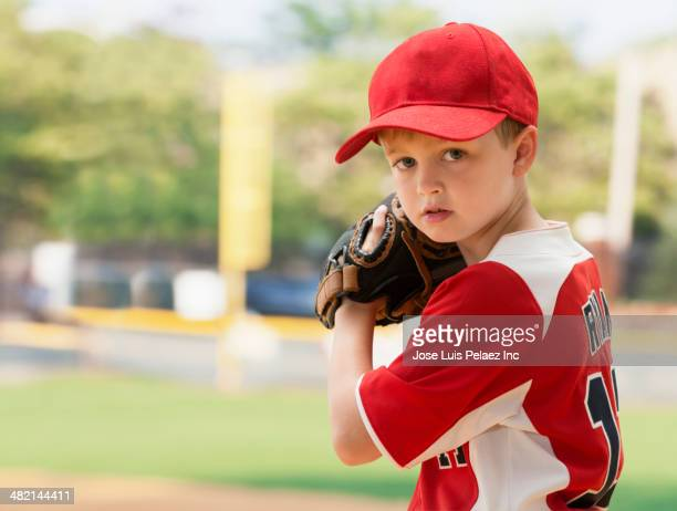 Serious Caucasian boy preparing to pitch in baseball game