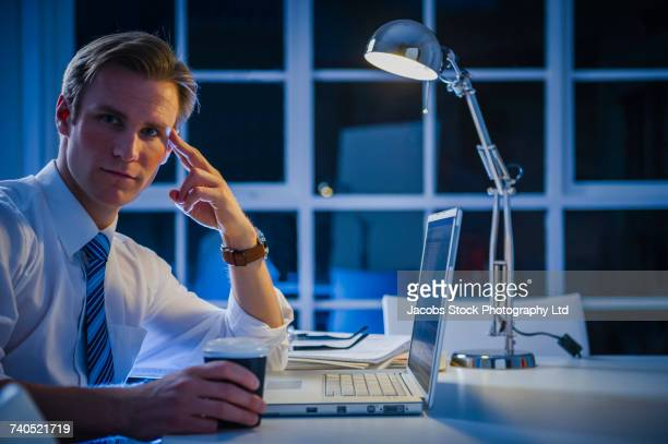 Serious Caucasian businessman using laptop and drinking coffee
