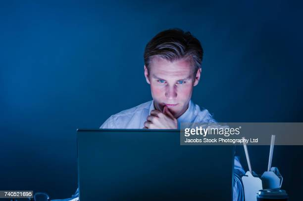 Serious Caucasian businessman using laptop