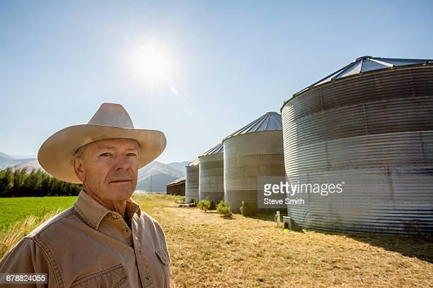 Serious Caucasian farmer near storage silos