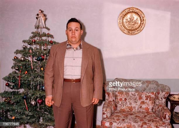 Serious Caucasian man posing near Christmas tree
