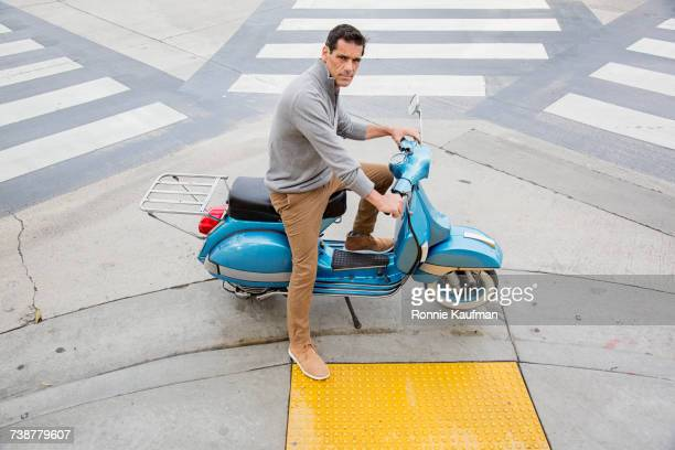 Serious Caucasian man sitting on scooter
