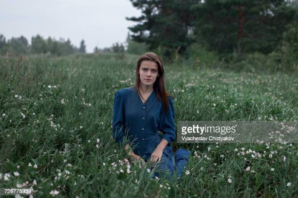 Serious Caucasian teenage girl sitting in field of wildflowers
