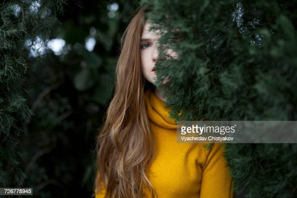 Serious Caucasian woman hiding behind tree