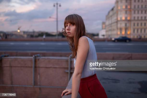 Serious Caucasian woman leaning on wall in city