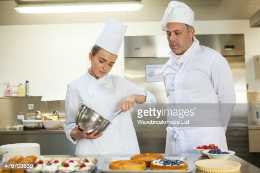 Serious chef whisking while being watched by head chef : Stock Photo
