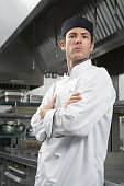 Portrait of a serious male chef with arms crossed in kitchen