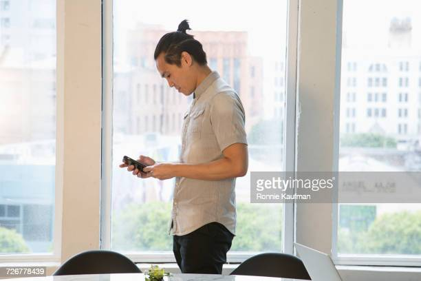 Serious Chinese businessman texting on cell phone in office