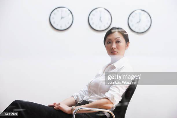Serious Chinese businesswoman sitting under clocks