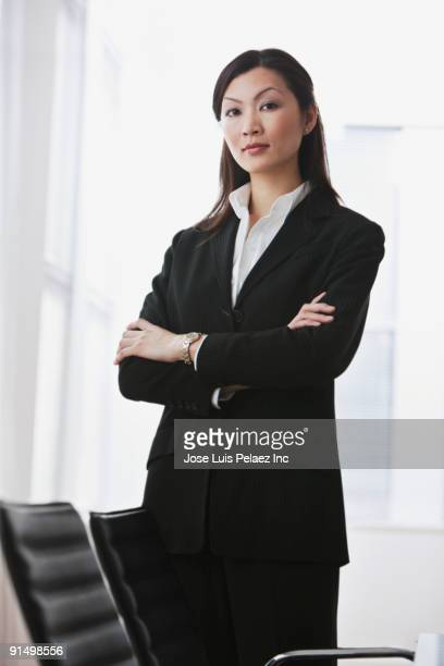 Serious Chinese businesswoman standing with arms crossed