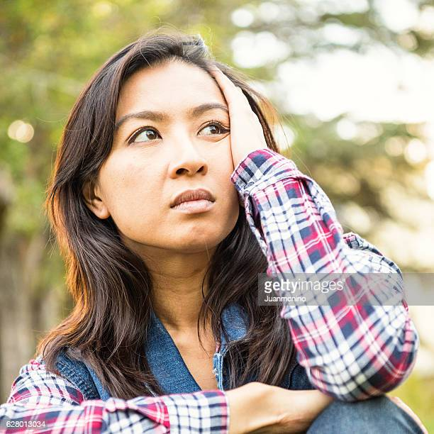 Serious concerned asian woman looking away