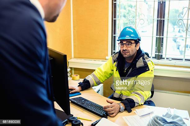 Serious construction worker in protective wear talking to man at desk