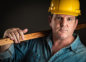 Serious Contractor in Hard Hat Holding Plank of Wood With Dramatic Lighting.