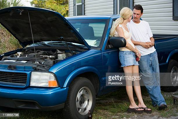 Serious couple conversing while leaning against old truck, in front of trailer home