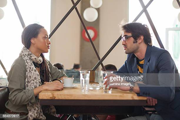 Serious couple talking in cafe
