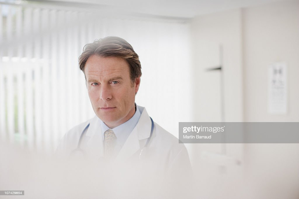 Serious doctor in doctors office : Stock Photo