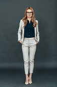 Full length of confident young woman in smart casual wear holding hands in pockets and looking at camera while standing against grey background