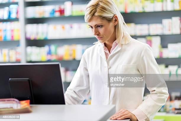 Schwere weibliche Apothekern mit computer in eine Apotheke.