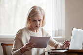 Serious frustrated middle aged senior woman worried reading bad news in paper letter document, stressed upset mature lady troubled with domestic bills, concerned about bankruptcy debt money problems