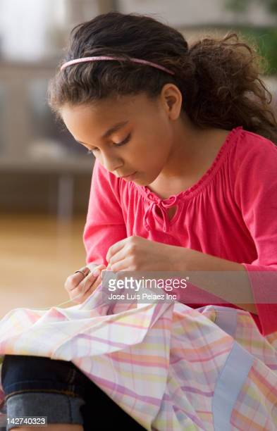 Serious girl sewing