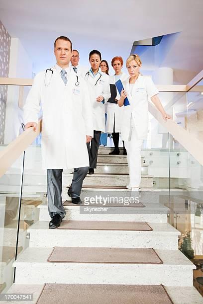 Große Gruppe von Ärzten gehen Sie die Treppen hinunter.
