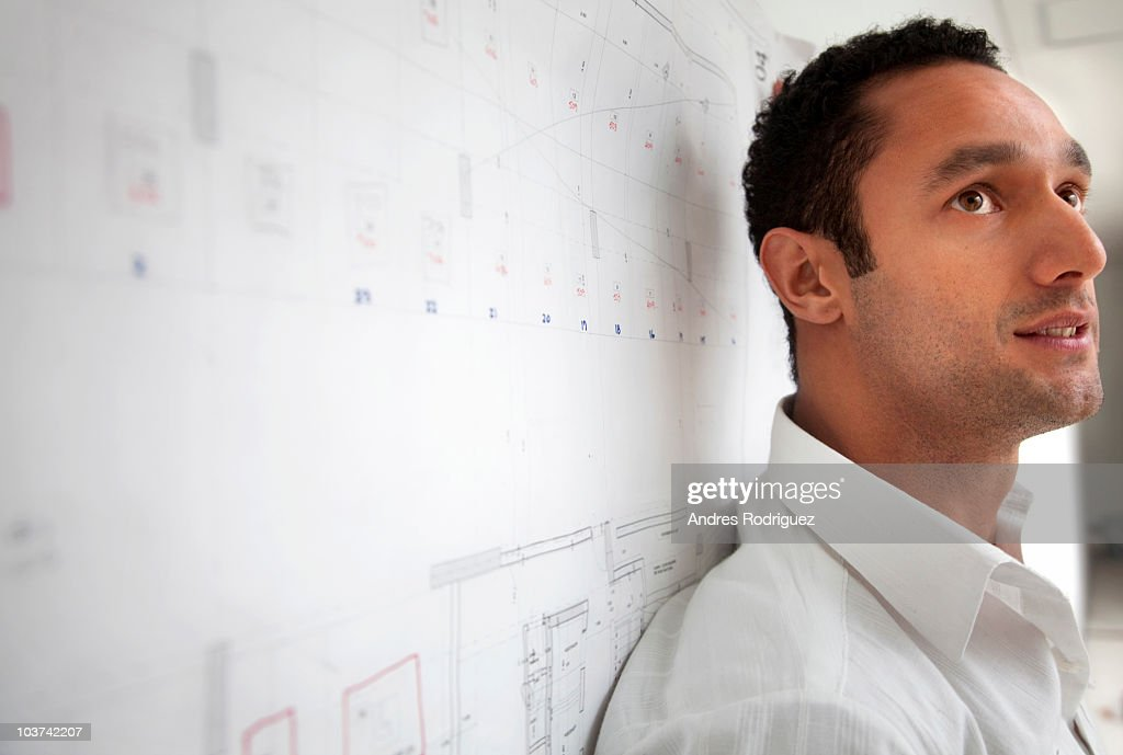 Serious Hispanic businessman leaning against blueprint : Stock Photo