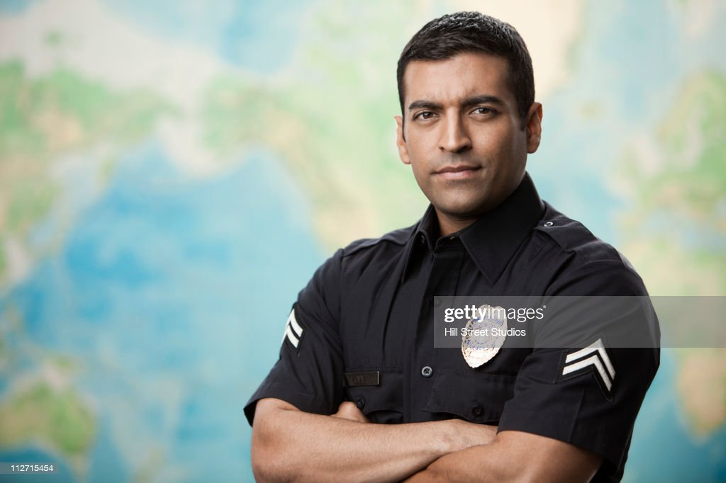 Serious Hispanic policeman with arms crossed